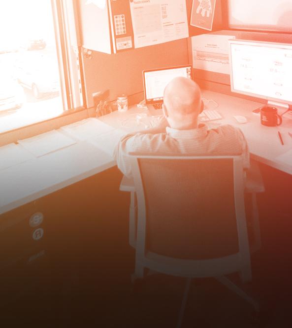 man facing computer at desk
